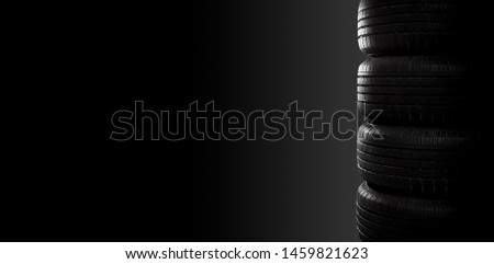Studio shot of four black car tires on black background with copy space. #1459821623