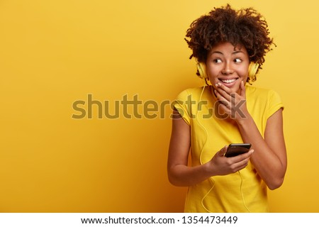 Studio shot of glad dark skinned curly teenager has fun indoor, listens pleasant melody in headphones, looks happily aside, wears bright yellow t shirt, feels relaxed. Monochrome. Hobby concept