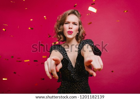 Studio shot of good-looking chilling woman having fun at event with confetti. Indoor portrait of happy laughing girl dancing in vintage attire.