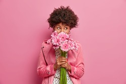Studio shot of good looking curly haired woman smells flowers, enjoys pleasant odor and stands in stylish clothes indoor. Lovely African American lady holds beautiful bouquet of gerbera daisy