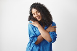 Studio shot of gorgeous charming young Afro American lady in stylish blue shirt having pleased happy facial expression, closing eyes and smiling, embracing herself, full with love and appreciation