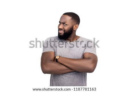 Studio shot of handsome african american coworker in trendy striped t-shirt, leaning head on fist while standing on white background, smirking and looking pleased at camera, being proud of art work