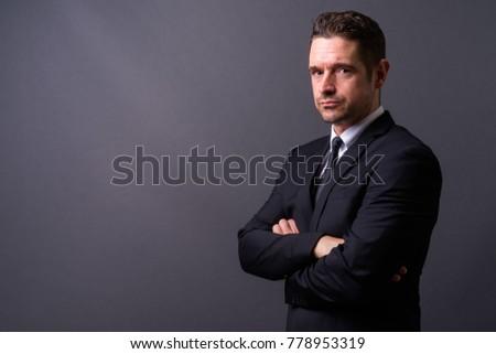 Studio shot of handsome businessman against gray background