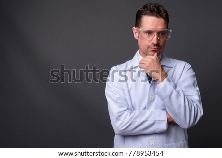 Studio shot of handsome man doctor wearing protective glasses against gray background #778953454
