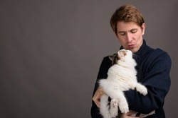 Studio shot of handsome man holding cute cat while wearing blue coat for cold weather against gray background
