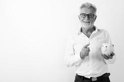 Studio shot of handsome senior bearded businessman against white background in black and white