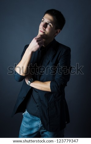 Studio shot of handsome thoughtful man on dark background