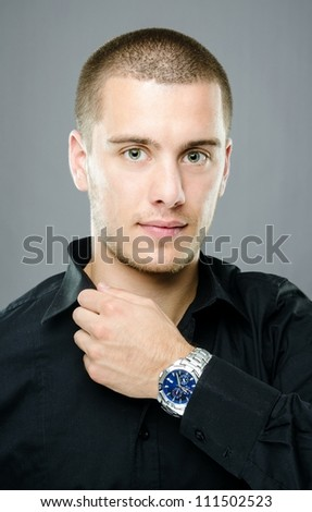 Studio shot of handsome young man with blue luxury watch