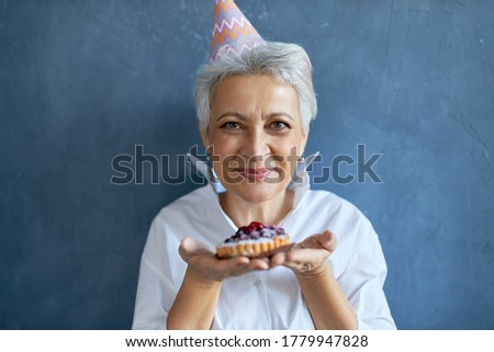 Studio shot of happy beauitful middle aged female wearing conical hat celebrating birthday, posing isolated with cake in her hands, offering you to have bite. Selective focus on woman's face
