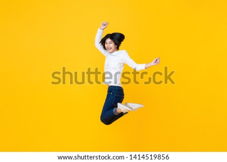 Studio shot of happy energetic asian woman wearing casual clothes jumping in mid-air isolated in yellow background