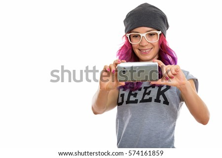 Studio shot of happy geek girl smiling while taking picture with mobile phone