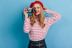 Studio shot of happy girl in striped shirt holding camera. French female model taking photos on blue background.