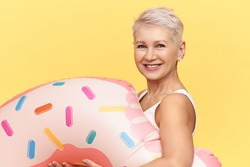 Studio shot of happy positive mature Caucasian woman with pixie hairdo carrying inflatable circle in shape of pink doughnut, going to swim in lake or sea during summer vacations, smiling joyfully