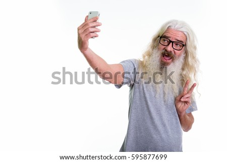 Studio shot of happy senior bearded man smiling and giving peace sign while taking selfie picture with mobile phone