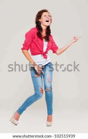 studio shot of happy woman playing air guitar over grey background