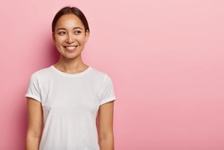 Studio shot of happy young Asian woman has tender smile, looks aside with charming expression, wears casual white t shirt, has natural beauty, isolated on pink wall. People and emotions concept