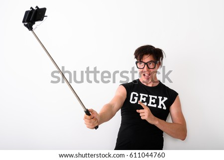 Studio shot of happy young nerd man smiling while taking selfie picture with mobile phone on selfie stick and pointing finger at phone while wearing shirt with geek text against white background