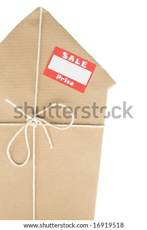 Studio Shot Of House Wrapped In Brown Paper With Sale Sticker - stock photo
