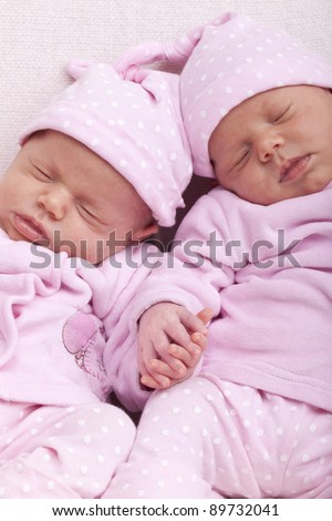 studio-shot of identical ( similar ) newborn babies. twin sisters sleeping and holding hand.