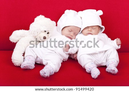 studio-shot of identical ( similar ) twin baby sisters resting and sleeping on a red sofa.