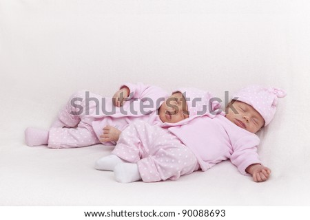 studio-shot of identical twin girls sleeping on a sofa. - stock photo