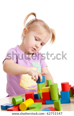 studio shot of little girl playing with toy blocks