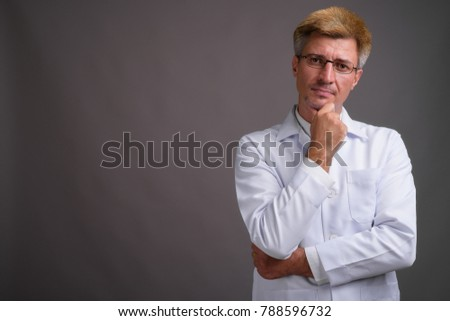 Studio shot of man doctor with blond hair against gray background