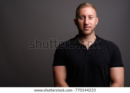 Studio shot of man with blond hair wearing black shirt against gray background #770144233