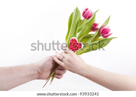 studio-shot of mans hand giving woman's hand a flower bouquet with red/white tulips and a wooden heart shape, on a white background.