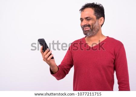 Studio shot of mature bearded Indian man against white background #1077211715