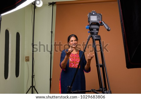 Studio shot of mature beautiful Indian woman against brown background - Shutterstock ID 1029683806
