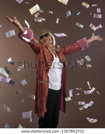 Studio shot of money falling on senior woman