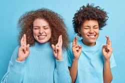 Studio shot of multiethnic women stand next ot each other cross finger for good luck anticipate positive news or result close eyes pose optimistic drssed casually isolated over blue background