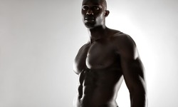 Studio shot of muscular man posing against grey background. Shirtless male african model with muscular build looking away.