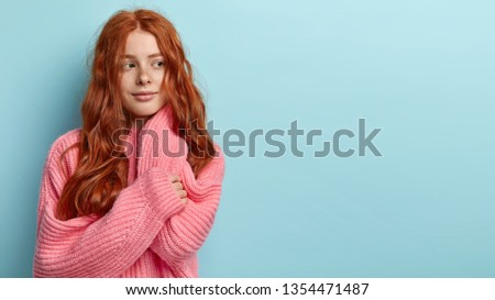 Studio shot of pensive long haired foxy teenager dressed in oversized knitted jumper, looks pensively aside, dreams about something during cold winter day, isolated over blue wall with empty space