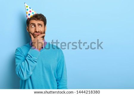 Studio shot of pensive unshaven guy focused aside, being deep in thoughts, thinks over ideas for awesome party, wears neat blue sweater and paper hat, touches chin, wants to make surprise for friend