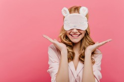 Studio shot of pleased beautiful young woman posing in eyemask. Cheerful european girl in pajamas standing on pink background in sleep mask in morning.