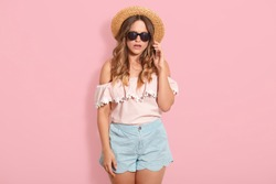 Studio shot of pretty woman wearing blouse, short, straw hat and sunglasses, having conversation via smart phone, model posing isolated over pink studio background. People and technology concept.