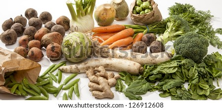 Studio shot of raw vegetables crowded on a white surface.
