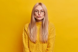 Studio shot of romantic blonde young woman keeps lips rounded wants to kiss someone wears knitted sweater isolated over yellow background. Lovely woman sends mwah to you. Face expresions concept