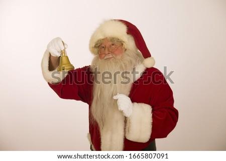 Studio shot of Santa Claus ringing bell