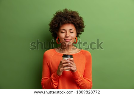 Studio shot of satisfied dark skinned girl with Afro hair holds paper cup of hot coffee, closes eyes, wears orange jumper, green background. Beautiful young woman enjoys aromatic cappuccino.