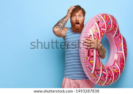 Studio shot of scared redhead man recreats during summer holidays, holds pink swimring, shocked to forget necessary thing for rest, wears striped sailor vest and shorts keeps hand on head. Omg concept
