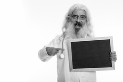 Studio shot of senior bearded man doctor isolated against white background in black and white