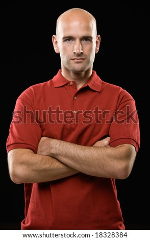 Studio shot of serious bald man posing with arms crossed
