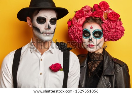 Studio shot of serious couple wears vivid makeup, celebrate traditional mexican holiday, wear wreath made of flowers, come on costume party, isolated over yellow background. Day of Death concept