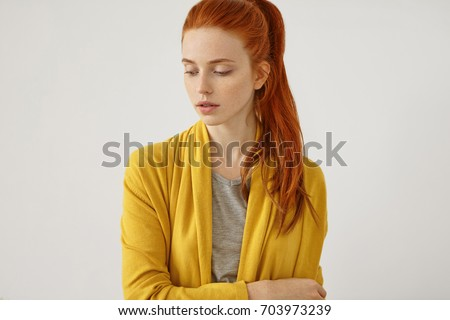 Studio shot of serious red-haired female with freckled skin with no make-up, wearing yellow cape, standing crossed hands over white background. Beautiful woman with reddish ponytail, looking down Foto stock ©