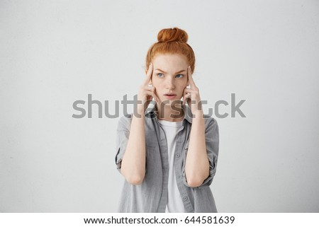 Studio shot of serious redhead young Caucasian woman holding fingers on her temples and looking up sideways with concentrated and focused expression, as if trying to remember something important