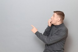 Studio shot of shocked frightened mature man wearing jumper, being full of fear, biting nails, pointing with finger at something awful, standing sideways over gray background, copy space on left
