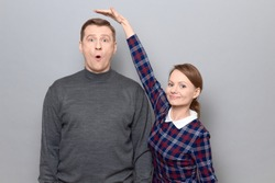 Studio shot of short woman standing and showing height of tall man, woman is smiling, man is amazed, over gray background. Concept of diversity of people's heights, tall and short persons